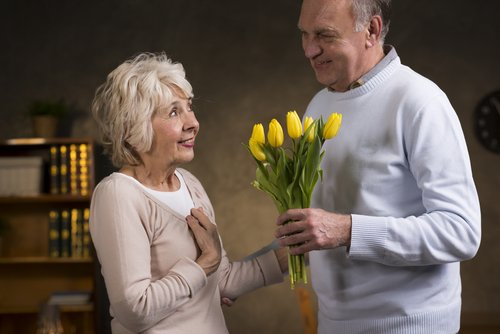 Example of a random act of kindness, an elderly couple where the husband is giving his wife flowers.