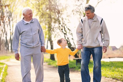 Grandfather, father, and son walking through the park.