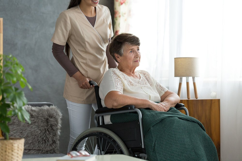 Woman caregiver pushing elderly patient in a wheel chair